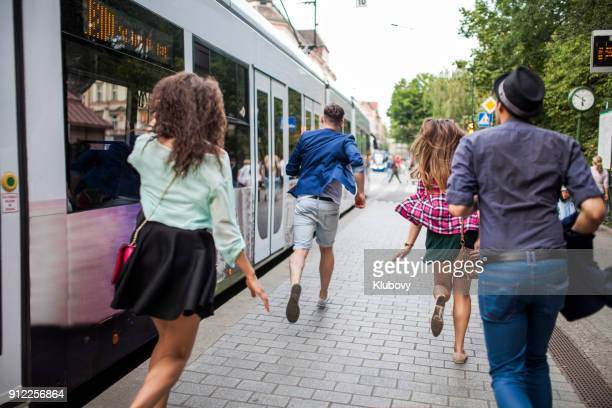 group of young people on a bus/tram stop - istantanea foto e immagini stock
