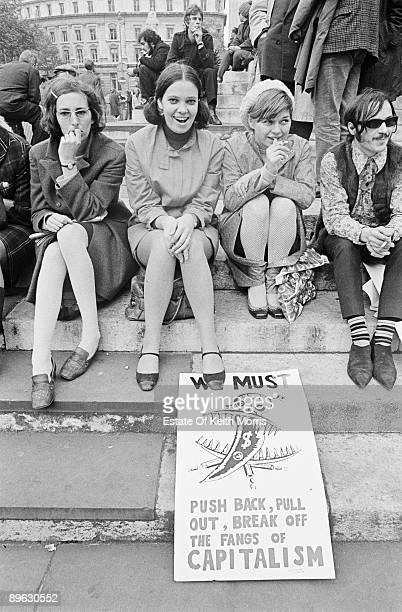 A group of young people on an anticapitalist demonstration London 1968 Their placard reads 'We must push back pull out break off the fangs of...