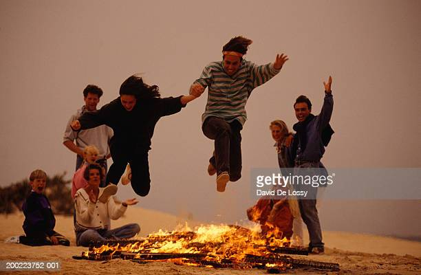 Group of young people on beach, two women jumping over bonfire