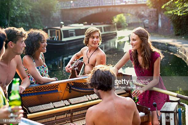 group of young people on canal boat - stringed instrument stock pictures, royalty-free photos & images