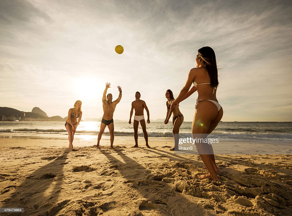 Group of young people playing beach volleyball at sunset. : Stock Photo