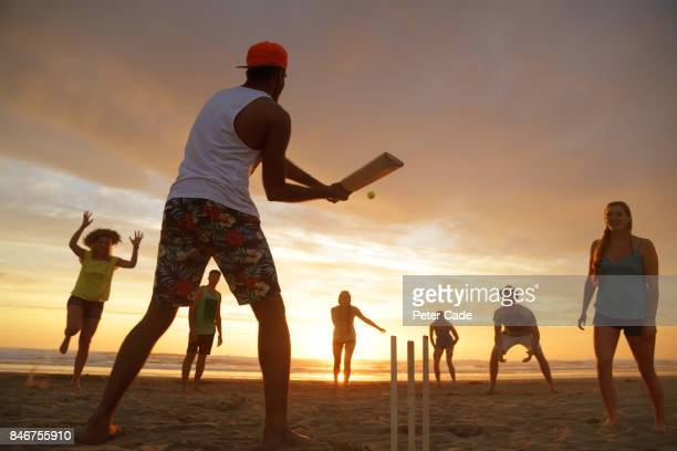Group of young people playing cricket on beach at sunset