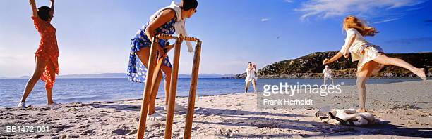 group of young people playing cricket on the beach - beach cricket stock pictures, royalty-free photos & images