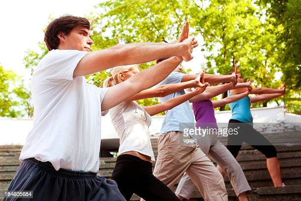 Group of Young People Practicing Tai Chi Outdoor