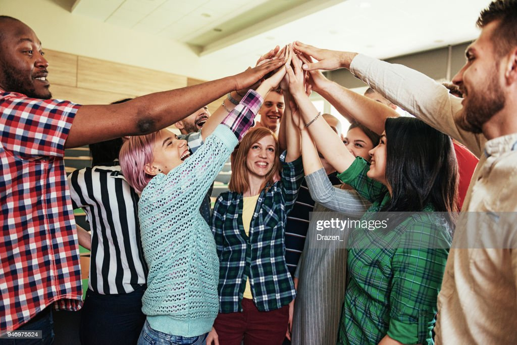 Group of young people putting arms up together : Stock Photo