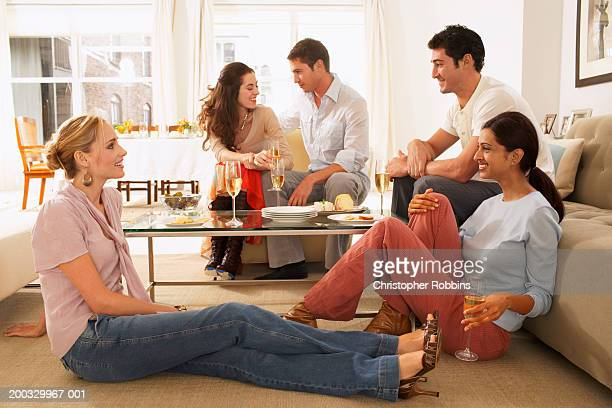 Group of young people relaxing around coffee table, drinking champagne