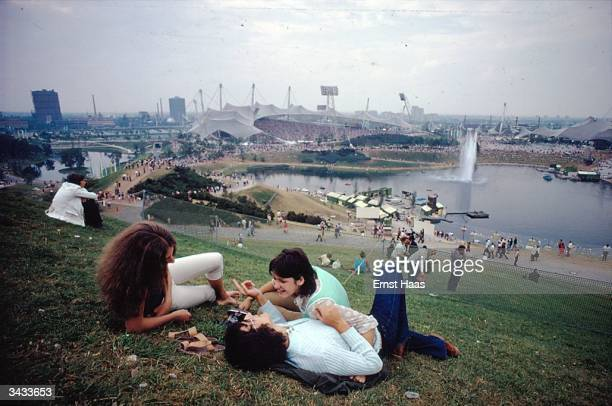 A group of young people relaxing on the grass in front of Munich's Olympic stadium In Germany book