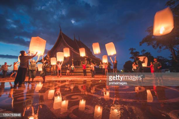 group of young people releasing lanterns in sirindhorn wararam phu prao temple - yi peng stock pictures, royalty-free photos & images