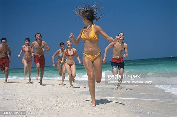 group of young people running on beach - swimwear stock pictures, royalty-free photos & images
