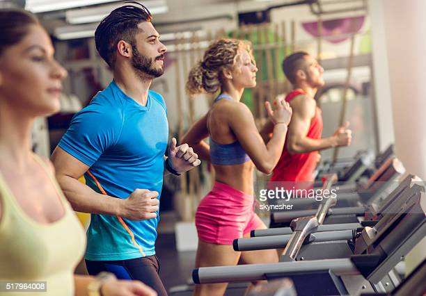 Group of young people running on treadmills in a gym.