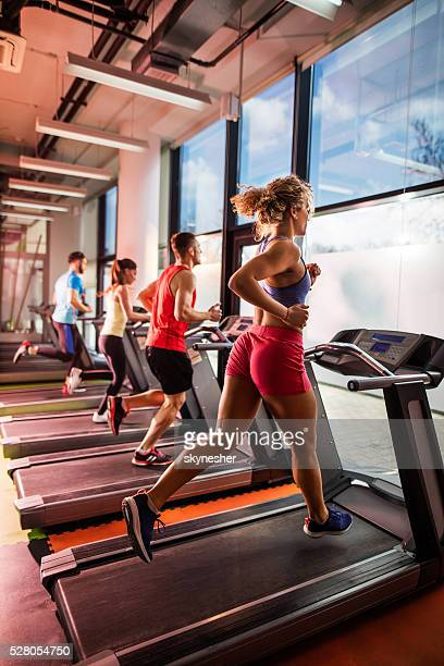Group of young people running on treadmills in gym.