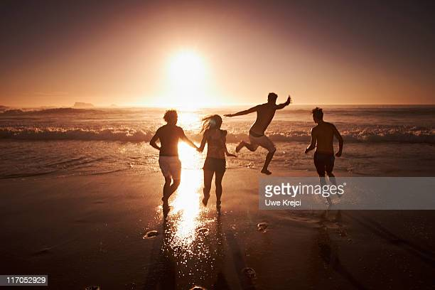 Group of young people running towards sea