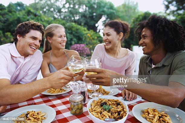 Group of young people seated outdoors at a dining table toasting with white wine