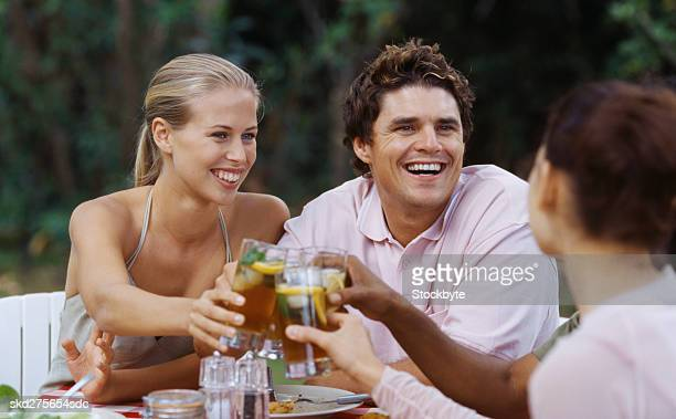 Group of young people seated outdoors at a dining table toasting with Ice tea