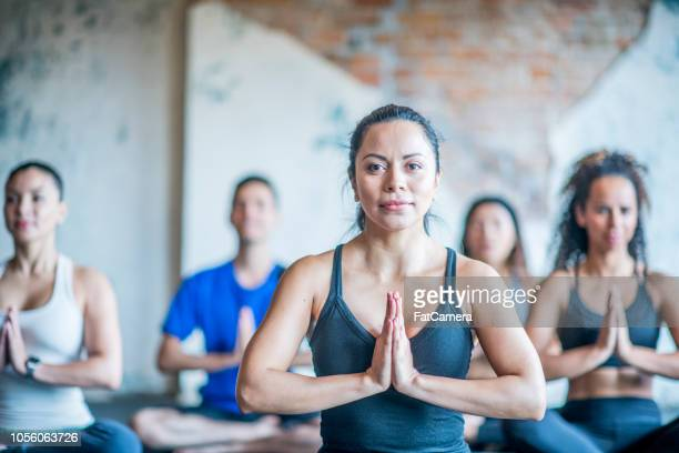 a group of young people sit in yoga pose - yoga studio stock pictures, royalty-free photos & images