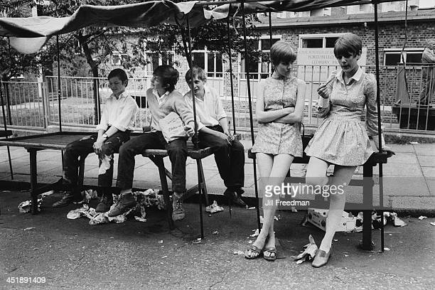 A group of young people sit on the empty market stalls in Portobello Road London circa 1969