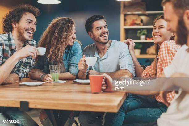 Grupo de jóvenes sentados y hablando en la cafetería