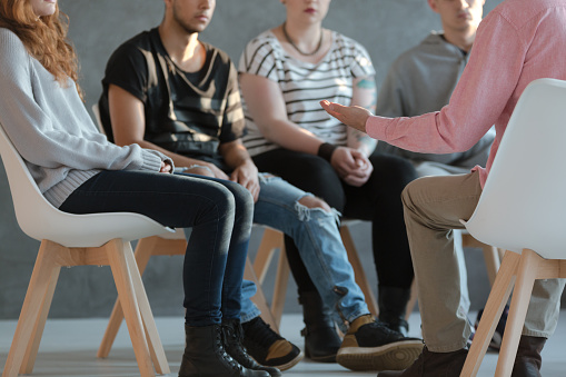 Group of young people sitting in a circle and talking to psychiatrist  during a therapy 1004109250