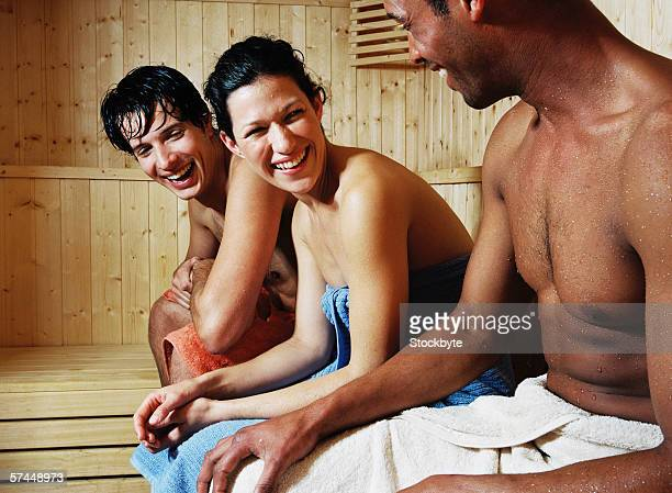 group of young people sitting in sauna smiling - black woman in sauna stock pictures, royalty-free photos & images