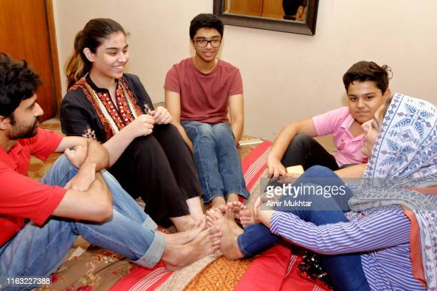 a group of young people sitting on a bed while massaging their feet - hijab feet stock photos and pictures