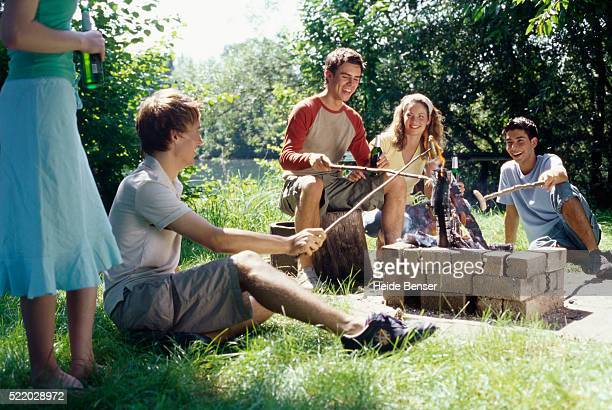 Group of young people sitting on a meadow having a barbecue