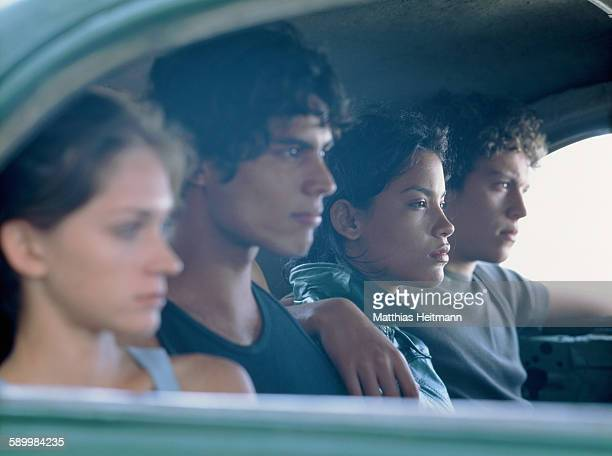 Group of young people sitting on the back seat of a car