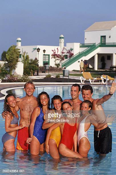 Group of young people standing in shallow end of swimming pool, waving, portrait