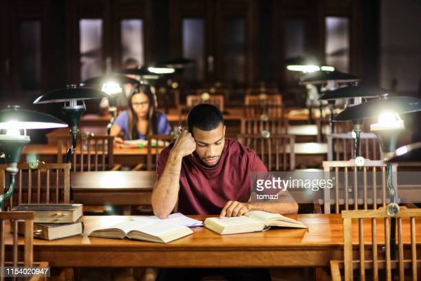 group of young people studying in library at night - science photo library stock pictures, royalty-free photos & images