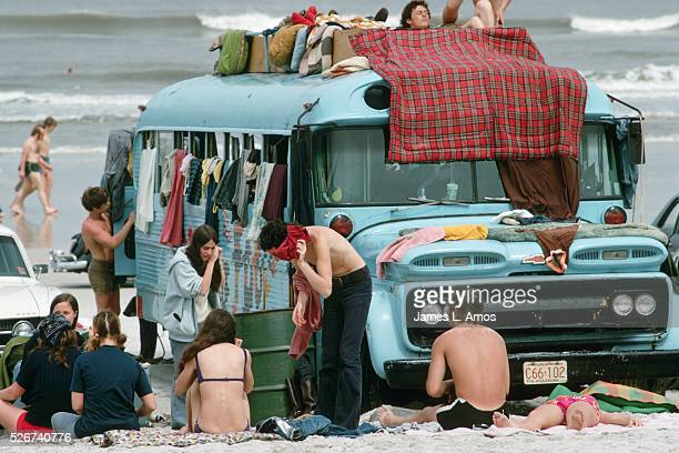 A group of young people sunbathe around a bus parked on Daytona Beach during Spring Break
