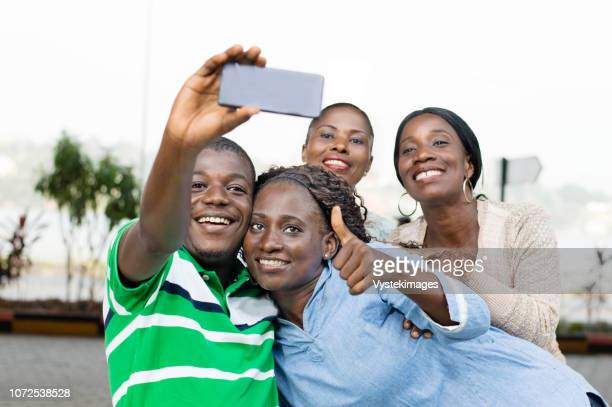 group of young people taking a picture with a mobile phone to mark their reunion. - côte d'ivoire stock pictures, royalty-free photos & images