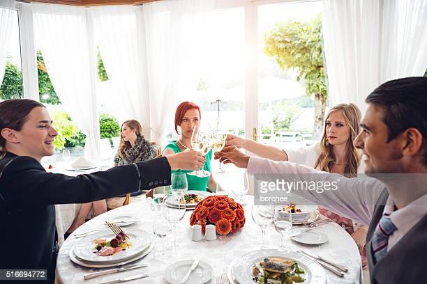 Groupe de jeunes gens portant un toast au dîner