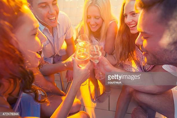 Groupe de jeunes gens portant un toast avec verres de vin.