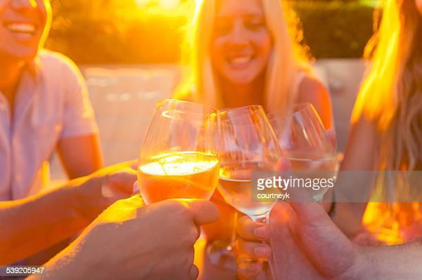 Gruppe von jungen Menschen Anstoßen mit Wein Gläser.