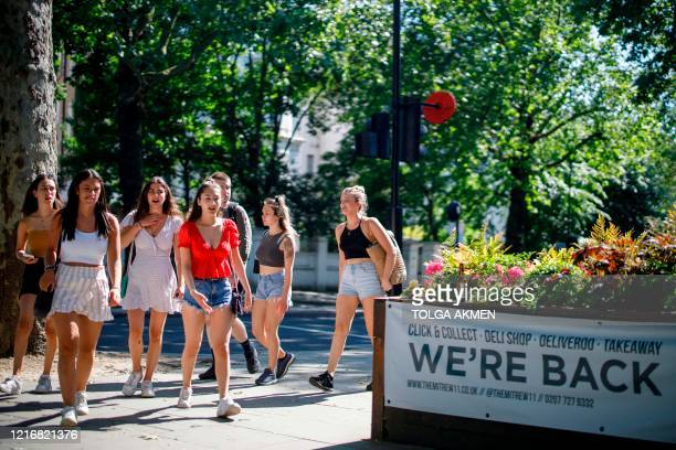 A group of young people walk past a pub open for takeaways on Holland Park Avenue in west London on June 1 following the easing of the lockdown...