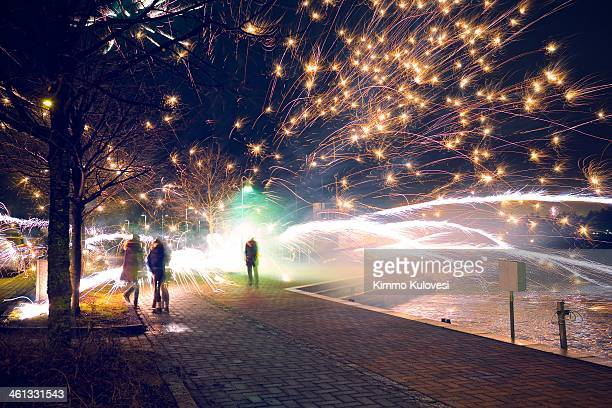 Group of young people watches as a firework explodes on the ground at midnight during New Year's celebrations in Herttoniemi, Helsinki, Finland.