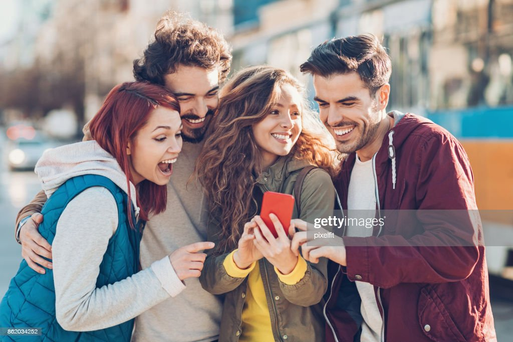 Group of young people watching at a smart phone and laughing : Stock Photo