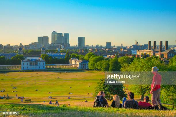 Group of young people watching sunset over London skyline from the Observatory Hill in Greenwich
