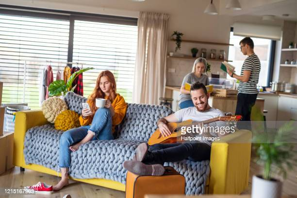 group of young people with guitar sitting on sofa at home, relaxing. - musical equipment stock pictures, royalty-free photos & images