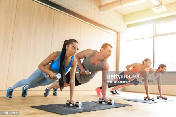 Group of young people workout with dumbbells in fitness