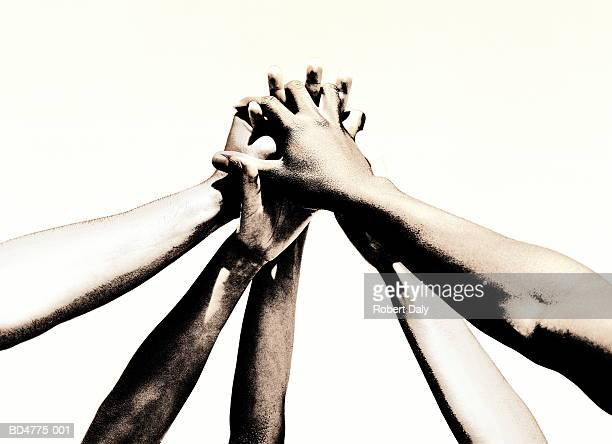 group of young people's hands clasped together (toned b&w) - solidarité photos et images de collection