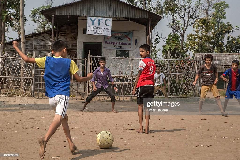 A group of young refugees play football on a field inside the Youth Friendly center funded by the UN High Commissioner for Refugees (UNHCR) in the Beldangi 2 refugee camp on March 14, 2015 in Beldangi, Nepal. More than 22,000 Bhutanese refugees still reside in the refugee camps set up in Nepal in the 1990s, after hundreds of thousands of Bhutanese fled the country following a campaign of ethnic cleansing by the Bhutanese Government against the country's ethnic Nepali population. After more than 20 years in Nepal, over 90% of the refugees have been successfully resettled in third countries, thanks to programs by UNHCR and IOM. Those remaining the camps are supported by several organizations that undertake a wide variety of projects. Helped by remittances sent back to Nepal by families already resettled in other countries, the refugees still in the camps have set up their own small businesses in the camps and the roads near them, roads which are also replete with Nepali-owned businesses who benefit directly from the refugees that are still waiting in Nepal to be resettled in third countries.