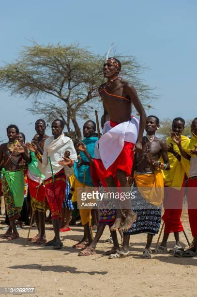 A group of young Samburu men dressed in traditional clothing performing a traditional jumping dance at a Samburu village near Samburu National...