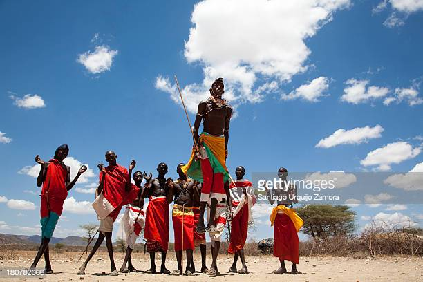 CONTENT] A group of young Samburu men dressed in traditional colorful red clothes wrapped around like a skirt performing their native dance in the...