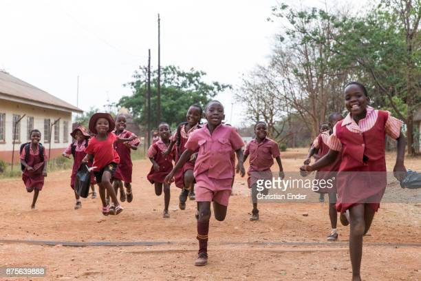 Group of young school boys with red school dress at the 'Sacred heart high school' in Banket are running to the photographer