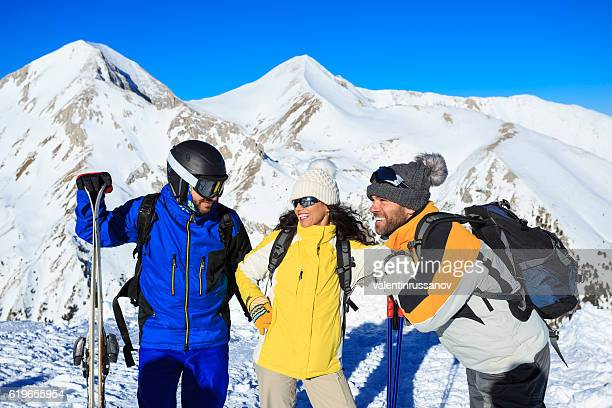 Group of young skiers resting on snow mountain