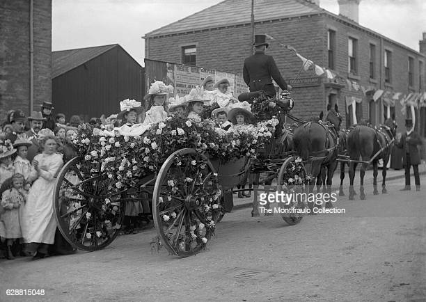 Group of young smartly dressed girls wearing wide brimmed hats and boys in straw tricorn hats sitting in a horse drawn carriage completely covered in...
