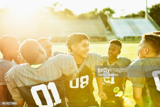 Group of young smiling football teammates gathered together on field cheering after game