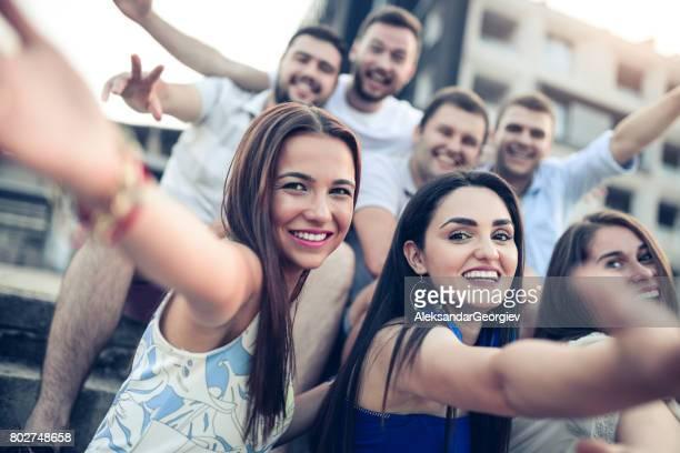 屋外の上げられた手で若い笑顔の人々 のグループ - パレード ストックフォトと画像