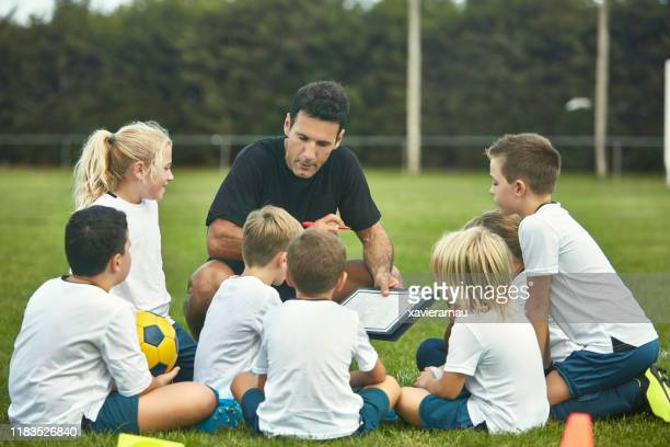 group of young spanish footballers studying play diagrams - sports training camp stock pictures, royalty-free photos & images