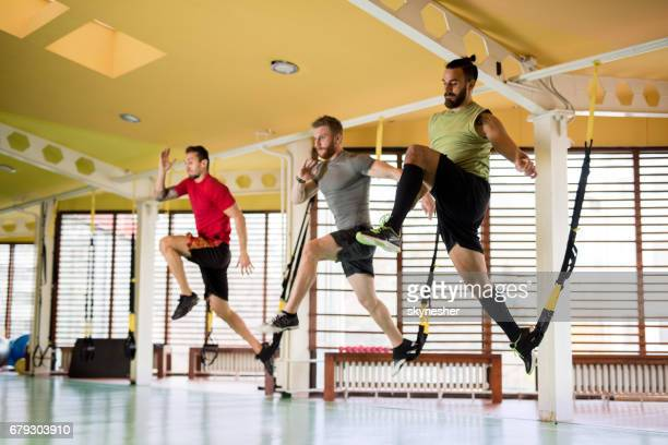 Group of young sportsmen having a suspension training in a gym.